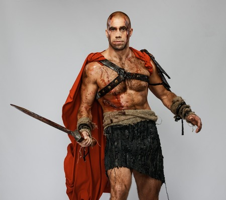 praetorian: Wounded gladiator with sword covered in blood isolated on grey