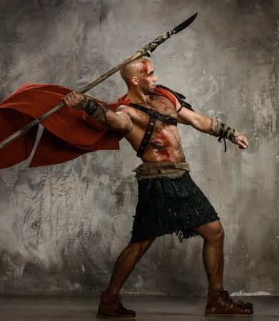 romano: Gladiador herido en rojo lanza lanzamiento abrigo Foto de archivo