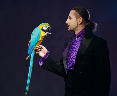 conjuror: Young handsome brunette magician man in stage costume with his trained parrot