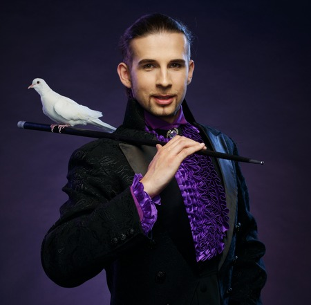 illusionist: Young handsome brunette magician man in stage costume with his trained white doves