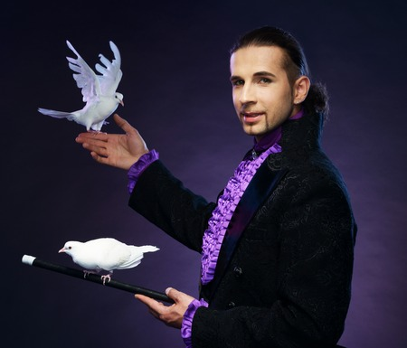 Young handsome brunette magician man in stage costume with his trained white doves photo