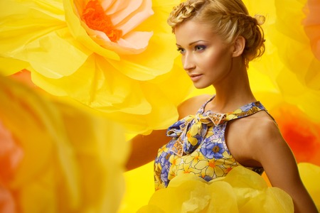 carelessness: Beautiful young cheerful blond woman in colourful dress among big yellow flowers