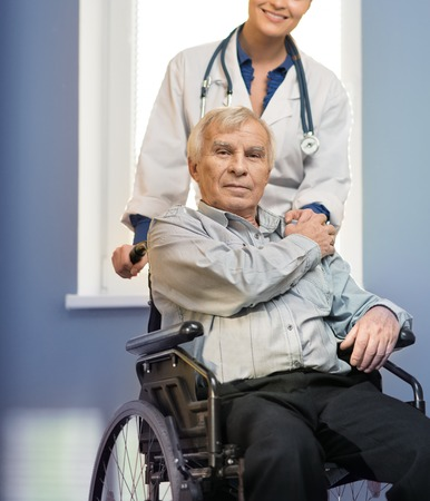 Cheerful young nurse woman with senior man in wheelchair  photo