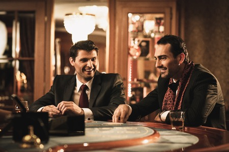 casino tokens: Two young men in suits behind gambling table in a casino