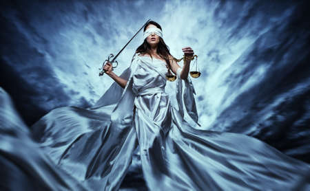 judgements: Femida, Goddess of Justice, with scales and sword wearing blindfold against dramatic stormy sky Stock Photo