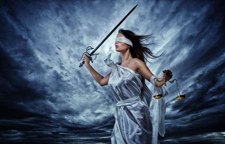 dama de la justicia: Femida, diosa de la justicia, con la balanza y la espada que llevan los ojos vendados contra el cielo tormentoso y dramático