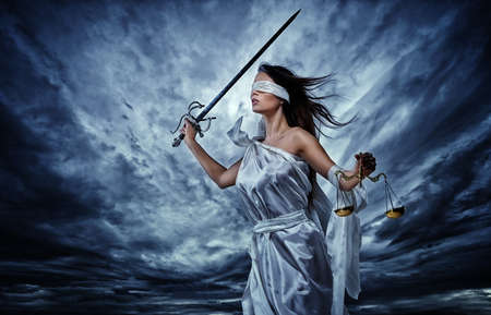 Femida, Goddess of Justice, with scales and sword wearing blindfold against dramatic stormy sky photo