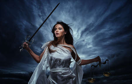 Femida, Goddess of Justice, with scales and sword against dramatic stormy sky photo