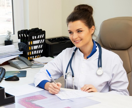 Cheerful young doctor woman in her office behind table  photo