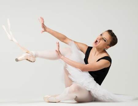 Young angry fed up ballerina dancer sitting on a floor  photo