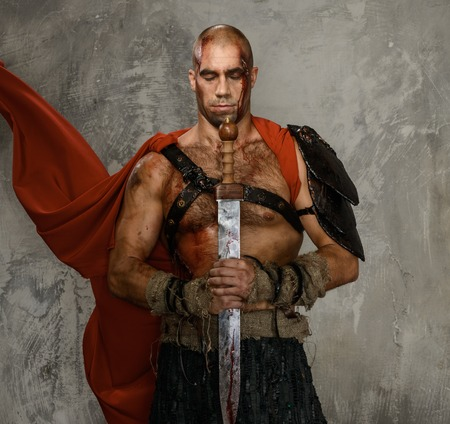 Wounded gladiator with  sword covered in blood isolated on grey photo