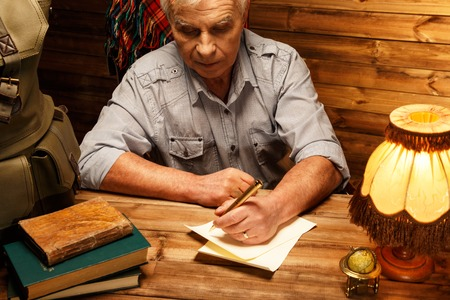 Senior writing letter with quill pen in homely wooden interior  photo