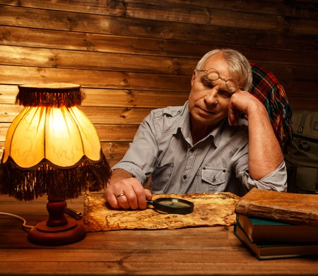 homely: Senior man with magnifier fell asleep in homely wooden interior  Stock Photo