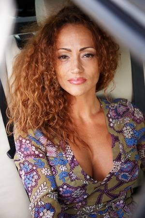 Beautiful middle-aged redhead woman in a luxury car interior  photo