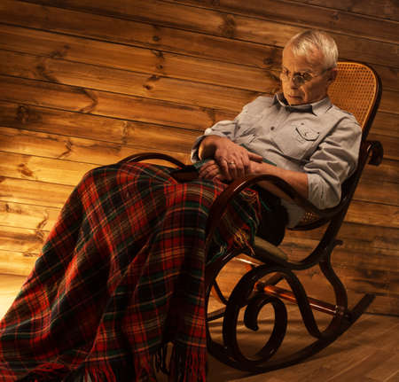 homely: Senior man fell asleep on rocking chair in homely wooden interior