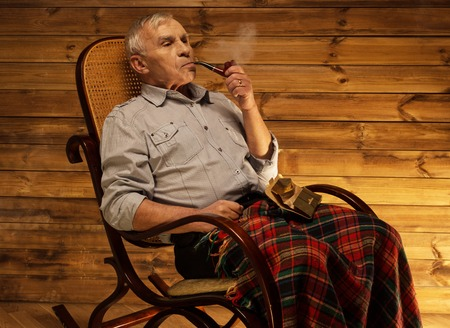 homely: Senior man with smoking pipe sitting on rocking chair in homely wooden interior Stock Photo