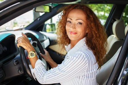 mature sexy woman: Beautiful smiling middle-aged redhead woman behind steering wheel Stock Photo