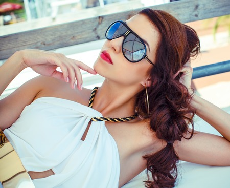 Beautiful brunette girl  in white summer relaxing outdoors photo