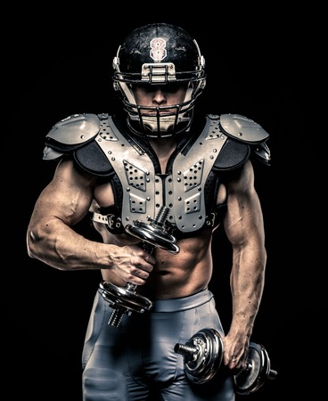 American football player with dumbbells wearing helmet and protective armour  photo