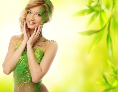 day spa: Beautiful young dreaming woman in conceptual spring costume touching her face