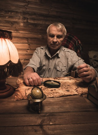 homely: Senior man with magnifier looking at vintage map in homely wooden interior