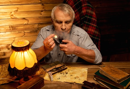 homely: Senior man with smoking pipe in homely wooden interior