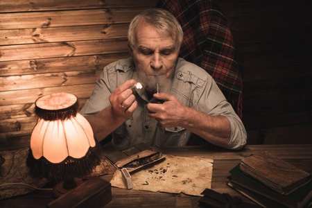 Senior man with smoking pipe in homely wooden interior  photo