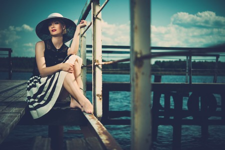 Beautiful woman wearing hat and white scarf sitting on old wooden pier  photo