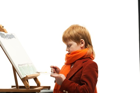 Little redhead boy drawing picture on an easel photo