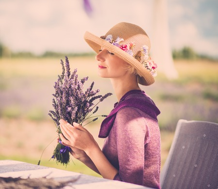 Woman in purple dress and hat behind table in lavender field  photo