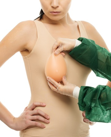 Plastic surgeon woman trying on silicon breast implant on client  photo