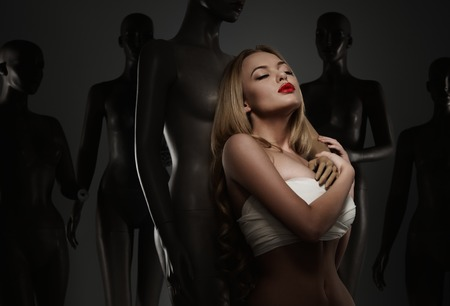 Young woman in bandage among mannequins - a plastic surgery concept  photo