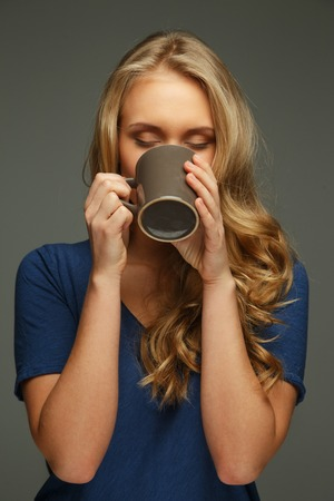 Positive young woman with long hair and blue eyes holding cup photo