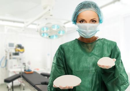 beaux seins: Plastique femme chirurgien tenant diff�rents implants mammaires taille de silicium � l'int�rieur de la salle de chirurgie