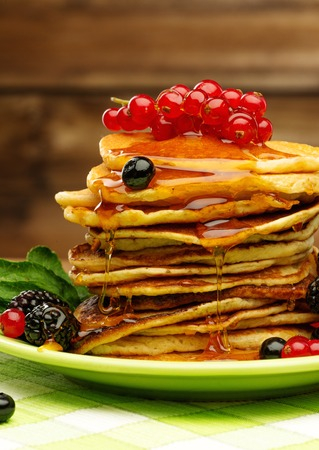 Tasty pancakes with maple syrup and fresh berries on a plate  photo