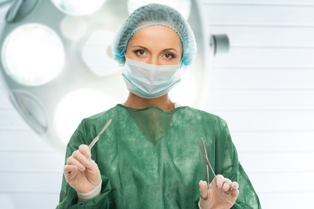 surgical mask woman: Young woman doctor with scalpel and scissors in surgery room interior  Stock Photo