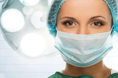 surgical: Joven médico mujer en la tapa y la máscara de la cara en el interior de sala de cirugía Foto de archivo