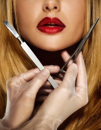 Manos con las herramientas de cirugía plástica cerca de la cara de mujer joven