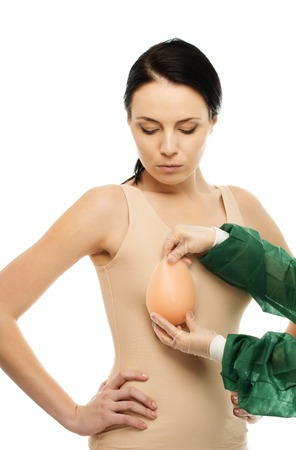Plastic surgeon woman trying on silicon breast implant on potential client  photo
