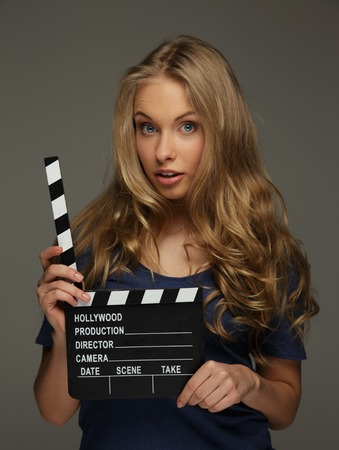 Young woman with long hair and blue eyes holding cinema clapper board photo