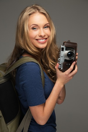 Positive young woman with long hair and blue eyes holding vintage style camera photo