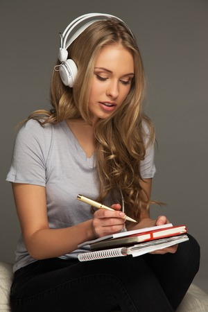 Young woman student with notebook listens to music photo