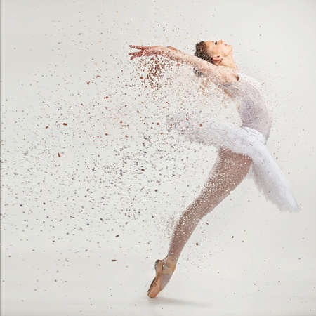 leap: Young ballerina dancer in tutu performing on pointes