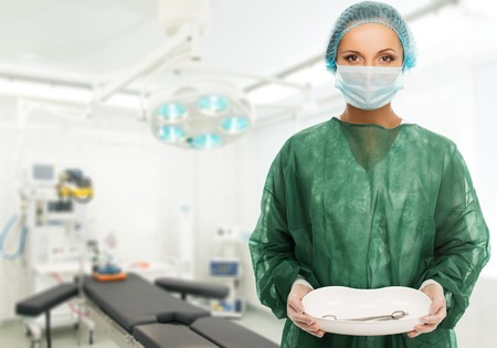 Young woman doctor in cap and face mask holding medicine tray with surgery tools  photo