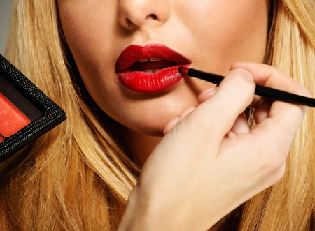 Mua artist painting red lips with tassel photo