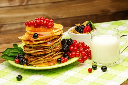 Healthy breakfast with pancakes, fresh berries and milk on tablecloth in rural interior  photo
