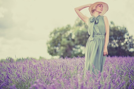 Woman in long green dress and hat in a lavender field  photo
