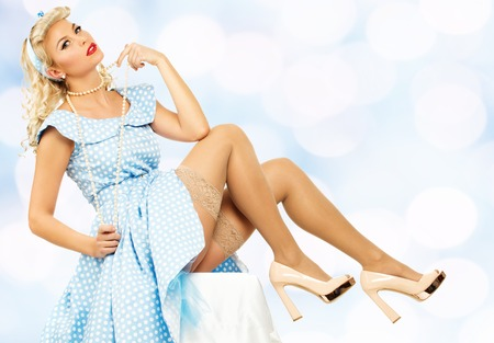 coquette: Sexy coquette blond pin up style young woman in blue dress