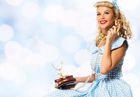 pin up vintage: Coquette bionda pin up stile giovane donna in abito blu con il telefono dell'annata Archivio Fotografico