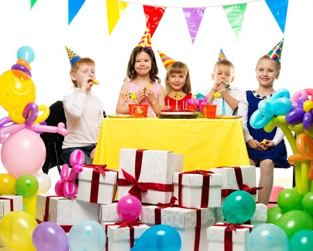 Croup of happy children celebrating birthday behind table  photo